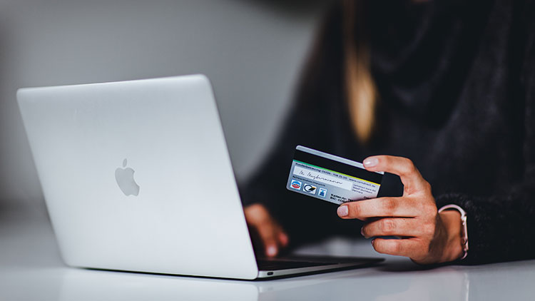 A woman enters her bank details while shopping online.