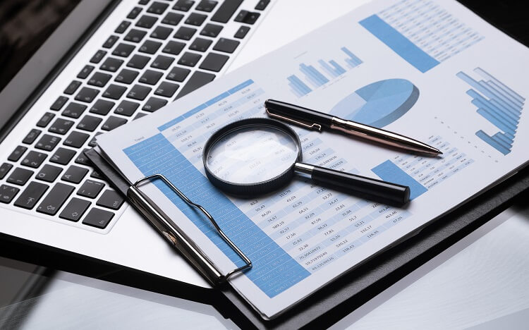 business documents, pen, magnifying glass with laptop