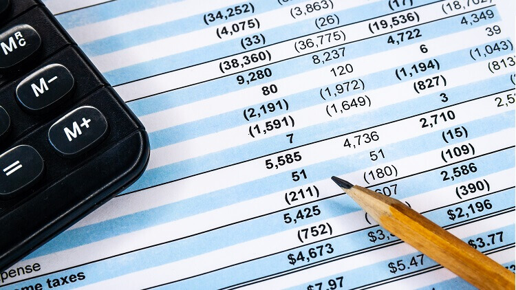 a pencil, a calculator placed on accounting financial report