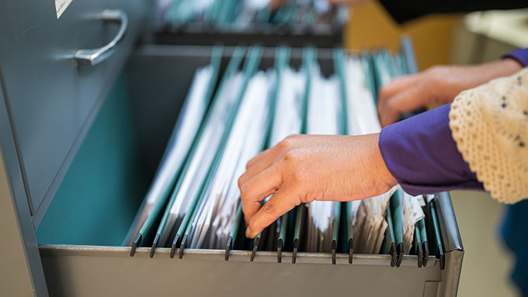 woman looking at piles of documents