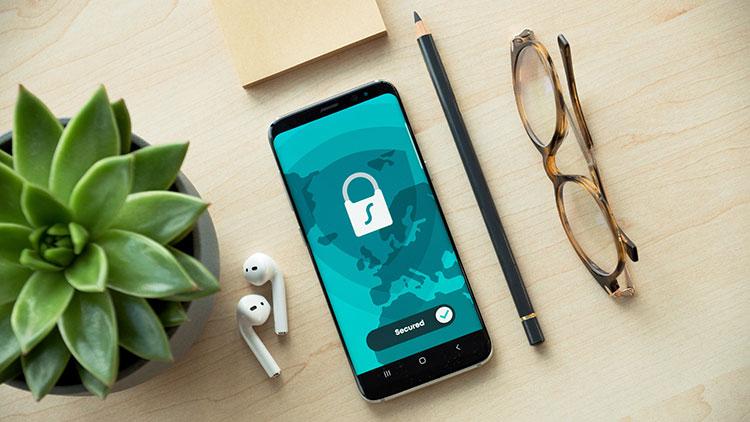 black iphone 5 besides brown framed glasses