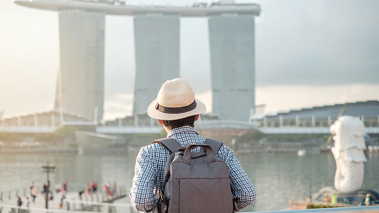 a man carrying a backpack looking at the marina bay in Singapore
