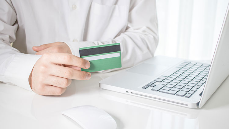 a man holds credit card and laptop