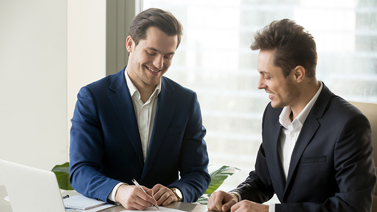 two men signing a contract