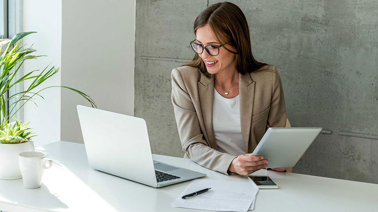 a business woman smiling and looking at her laptop