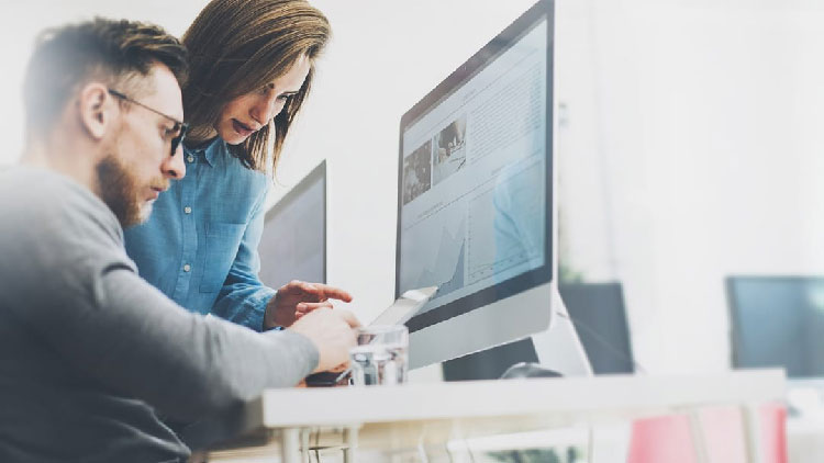 a man and a woman looking at desktop screen
